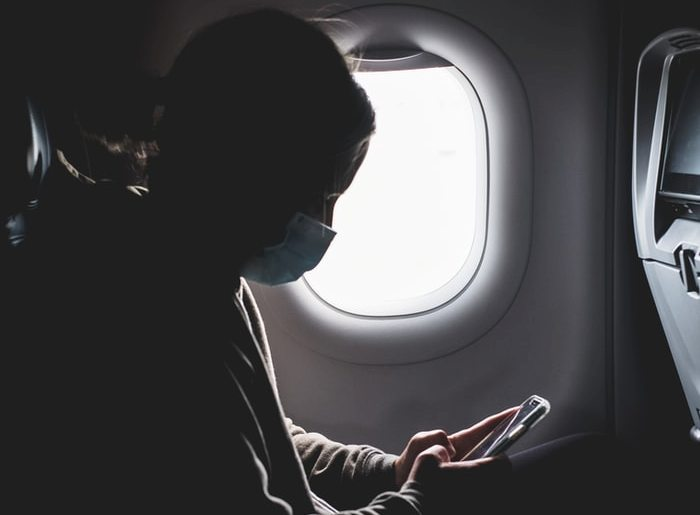 woman with face mask in a plane